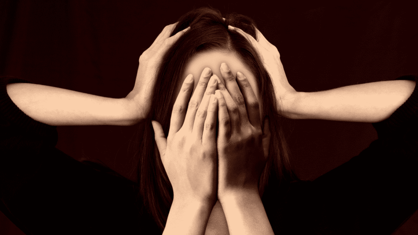 Lady with hands covering face depicting stress with someone else hands on sides of head